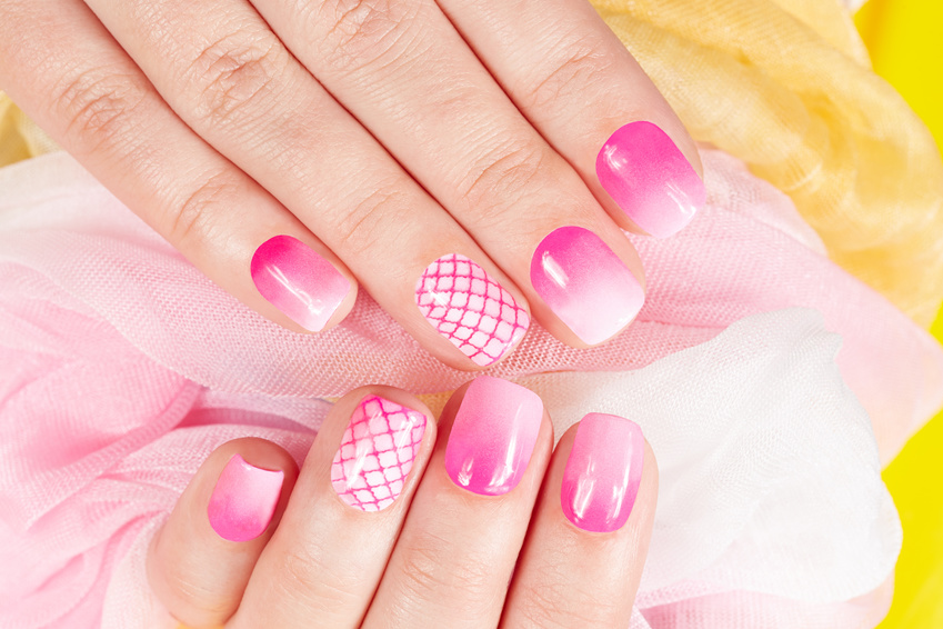 Hands with manicured nails covered with pink nail polish
